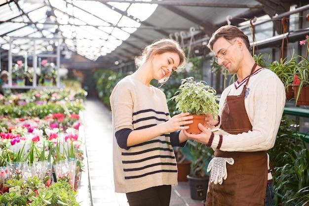 Vrolijke aantrekkelijke jonge vrouw met hulp van knappe man tuinman die bloemen in pot in tuincentrum kiest