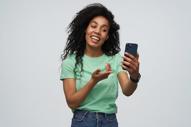 Vrolijke aantrekkelijke jonge vrouw met lang krullend haar in mint tshirt met smartphone en met videochat geïsoleerd over grijze muur gray