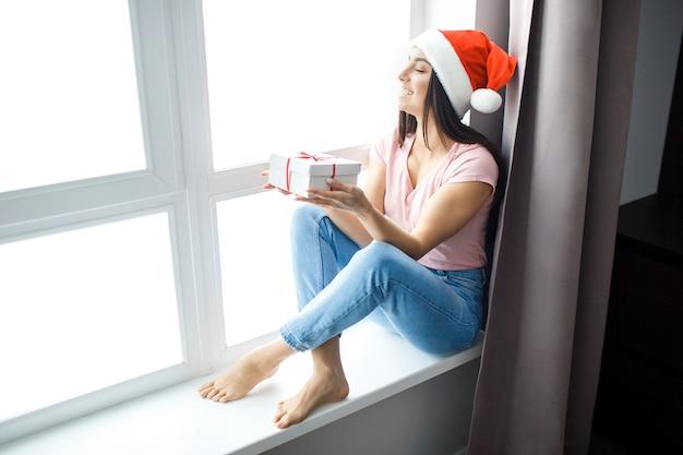 Vrolijke aantrekkelijke jonge vrouw zit aan het raam en kijkt ernaar. draag een rode hoed. kerst- of nieuwjaarsperiode. feestelijke stemming. alleen in de kamer.