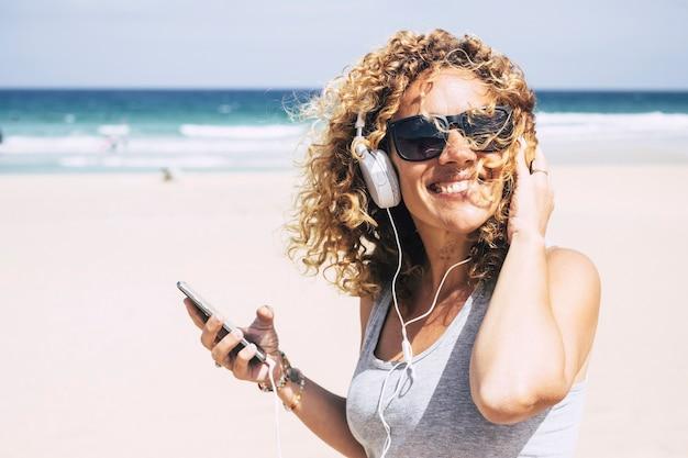 Vrolijke aantrekkelijke mooie blanke vrouw van middelbare leeftijd die lacht op het strand op een tropische plek terwijl je naar muziek luistert met de smartphone. mensen die genieten van vakantie en vrijheid van werkvakantie