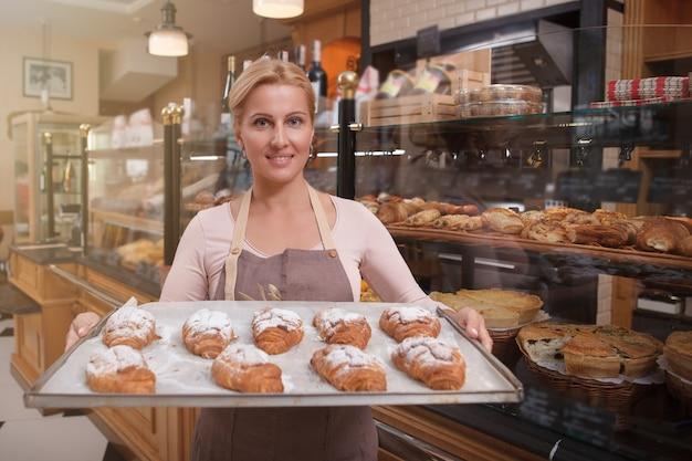 Vrolijke aantrekkelijke rijpe vrouw die vers gebakken croissants verkoopt bij haar bakkerij