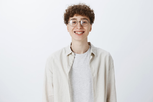 Vrolijke aantrekkelijke tiener man poseren tegen de witte muur