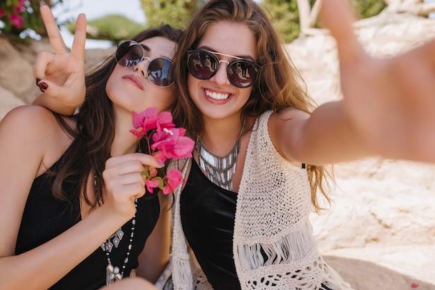 Vrolijke aantrekkelijke vrienden samen plezier maken en selfie maken op zomerverblijf. fascinerend meisje in gebreide retro kleding ontspannen met zus en lachen, tijd buiten doorbrengen