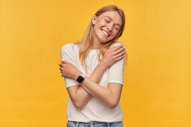 Vrolijke aantrekkelijke vrouw in wit t-shirt met sproeten en slimme horloge houdt de ogen gesloten en knuffelt zichzelf met de handen op geel