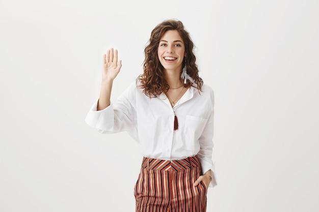 Vrolijke aantrekkelijke vrouw zwaaiende opgeheven hand om hallo, vriendelijke groet te zeggen
