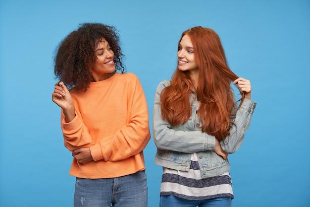 Vrolijke aantrekkelijke vrouwen die een lok van hun haar met opgeheven handen vasthouden en gelukkig naar elkaar kijken met een brede glimlach, geïsoleerd over blauwe muur