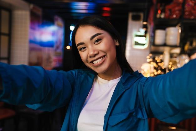 Vrolijke aardige aziatische vrouw die lacht en selfie neemt terwijl ze in café zit