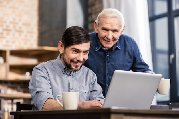 Vrolijke aardige man met laptop met zijn vader terwijl hij thuis samen rust