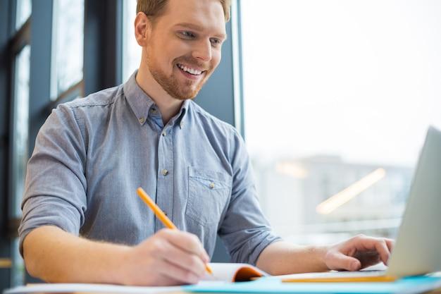 Vrolijke aardige positieve man aan tafel zitten en notities maken terwijl hij betrokken is bij zijn werk