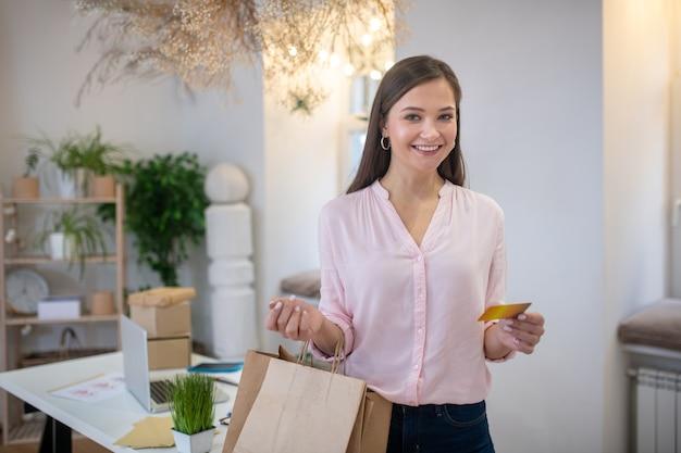 Vrolijke aardige vrouw stond met haar boodschappentassen na het winkelen