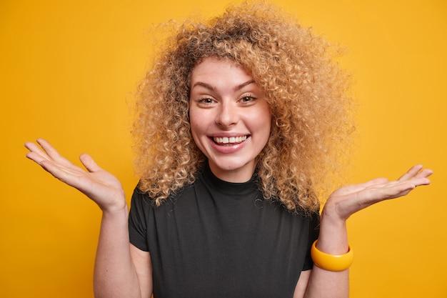 Vrolijke aarzelende vrouw met krullend haar spreidt handpalmen voelt terughoudend en onzeker glimlacht vreugdevol casual zwart t-shirt geïsoleerd over gele muur. twijfelachtig onzeker blij vrouwelijk model