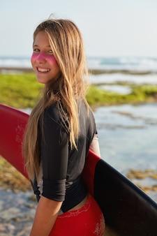 Vrolijke actieve surfboarder heeft een sportief lichaam, bereidt zich voor op een lokaal surftoernooi