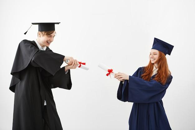 Vrolijke afgestudeerden glimlachend vechten met diploma's.