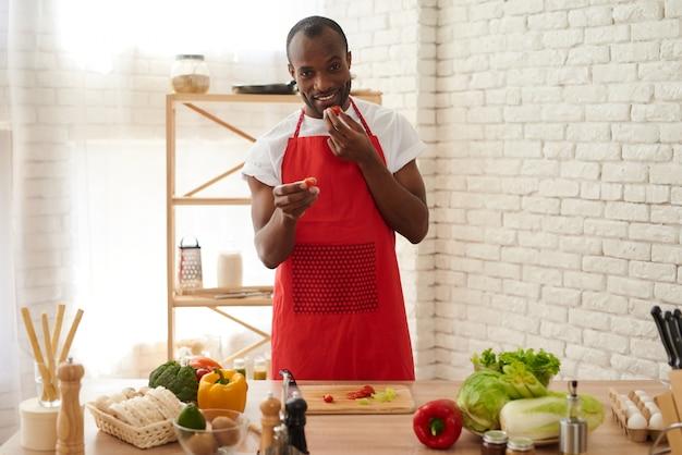 Vrolijke african american man in schort eet tomaten.