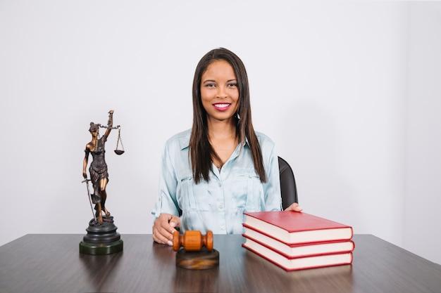 Vrolijke afrikaanse amerikaanse vrouw aan tafel met hamer, boeken en standbeeld