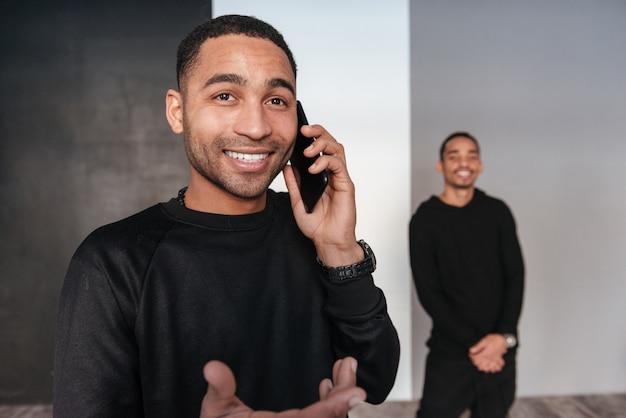 Vrolijke afrikaanse jonge mens die en op mobiele telefoon stading spreken