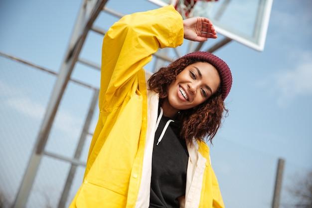 Vrolijke afrikaanse krullende jonge dame die gele laag draagt