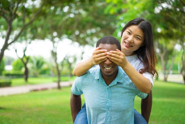 Vrolijke afrikaanse man die vriendin op de rug geeft terwijl ze zijn ogen met handen behandelt.