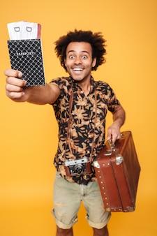 Vrolijke afrikaanse man met paspoort en koffer
