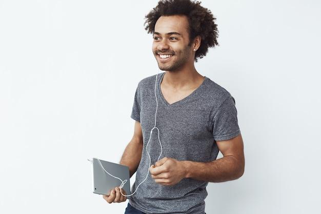 Vrolijke afrikaanse mens die in hoofdtelefoons holdingstablet glimlachen.
