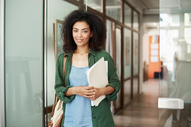 Vrolijke afrikaanse mooie studente het glimlachen holdingsboeken op universiteit. onderwijs concept.