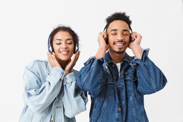 Vrolijke afrikaanse paar in denim shirts luisteren muziek door koptelefoon met gesloten ogen over grijze muur