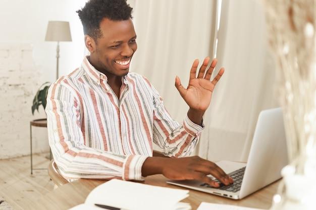 Vrolijke afrikaanse student zit open laptop breed glimlachend, groet tutor tijdens het online studeren met wifi.