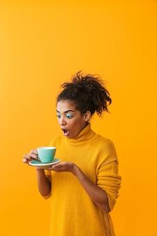Vrolijke afrikaanse vrouw die de kop van de sweaterholding op een geïsoleerde schotel draagt