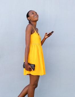 Vrolijke afrikaanse vrouw die met mobiele telefoon loopt