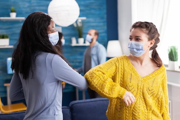 Vrolijke afrikaanse vrouw en haar vriend raken de elleboog aan en houden sociale afstand terwijl ze elkaar begroeten met een gezichtsmasker, om verspreiding van het coronavirus in de loop van de wereldwijde pandemie in de woonkamer te voorkomen