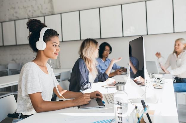 Vrolijke afrikaanse webontwikkelaar die aan een nieuw project werkt terwijl hij naar muziek luistert in een witte koptelefoon. zwarte vrouwelijke ontwerper doet haar werk in kantoor met pratende collega's.