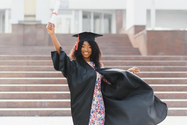 Vrolijke afro-amerikaanse afgestudeerde student met diploma in haar hand