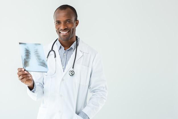 Vrolijke afro-amerikaanse arts die röntgenscan van de longen houdt tijdens het werken in het ziekenhuis