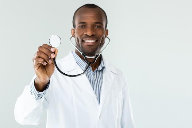 Vrolijke afro-amerikaanse arts met behulp van een stethoscoop tijdens het glimlachen