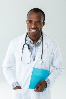 Vrolijke afro-amerikaanse arts met een medische geschiedenis tijdens het werken in een ziekenhuis