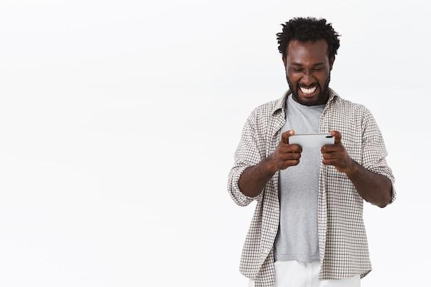 Vrolijke afro-amerikaanse bebaarde man speelt geweldig nieuw spel