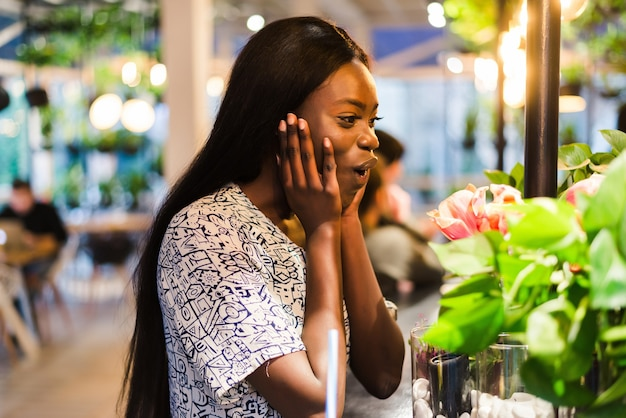 Vrolijke afro-amerikaanse jonge vrouw in zomerjurk in café is witte bloemen in vaas.