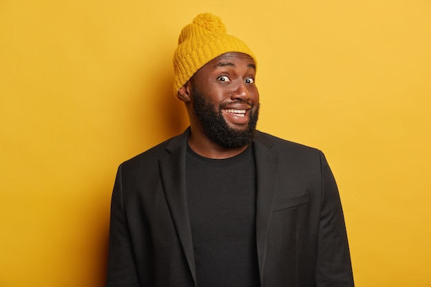 Vrolijke afro-amerikaanse man kijkt met nieuwsgierige blije uitdrukking