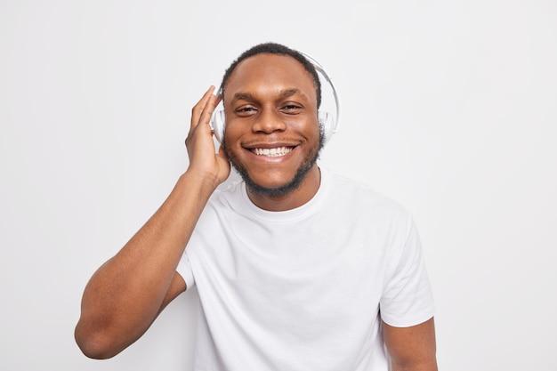 Vrolijke afro-amerikaanse man luistert naar favoriete muziek via een koptelefoon en lacht vrolijk