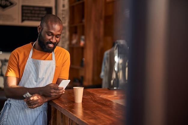 Vrolijke afro-amerikaanse man met behulp van mobiele telefoon in kapperszaak