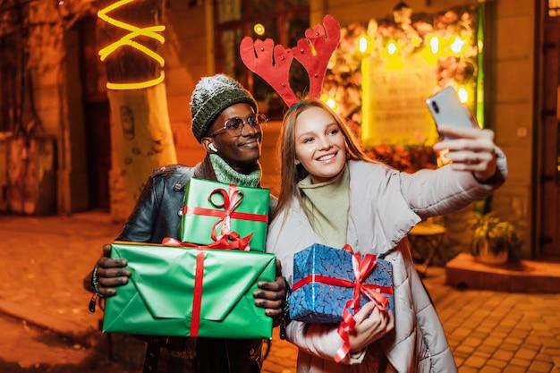 Vrolijke afro-amerikaanse man met blanke vrouw op straat terwijl het nemen van selfie foto op smartphone