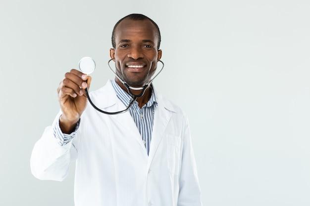 Vrolijke afro-amerikaanse man met een stethoscoop terwijl hij galdness uitdrukt