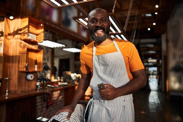 Vrolijke afro-amerikaanse man met tondeuse die in de kapperszaak staat