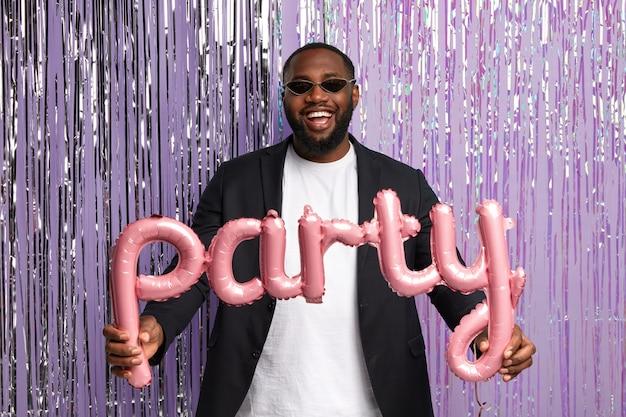 Vrolijke afro-amerikaanse mannelijke student afgestudeerd heeft een feestje met groepsgenoten na het verlaten van de universiteit, draagt stijlvolle zonnebril, formeel pak, houdt ballon in de vorm van letters, staat over klatergoud gordijn
