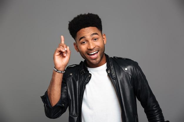Vrolijke afro amerikaanse stijlvolle man wijst met vinger omhoog, op zoek
