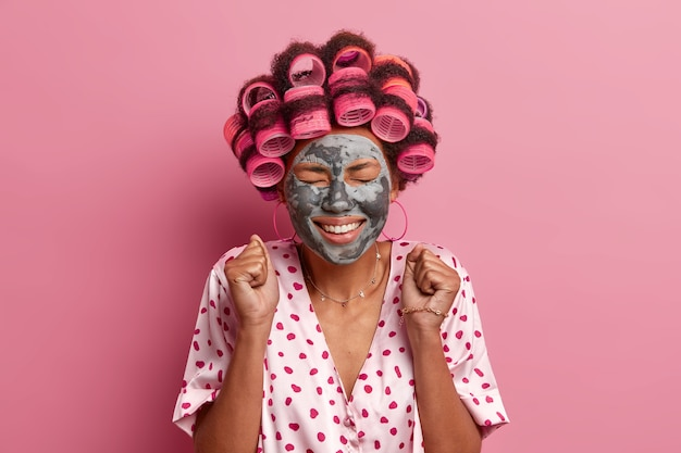 Vrolijke afro-amerikaanse vrouw balde vuisten, wacht op mooi effect van kleimasker, sluit ogen en lacht breed, past haarrollers toe, kleedt nonchalant, poseert