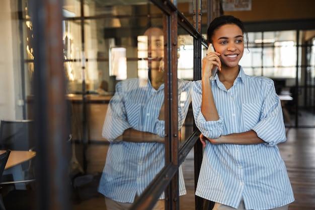 Vrolijke afro-amerikaanse vrouw die op mobiele telefoon praat en glimlacht terwijl ze op een glazen wand in een modern kantoor leunt