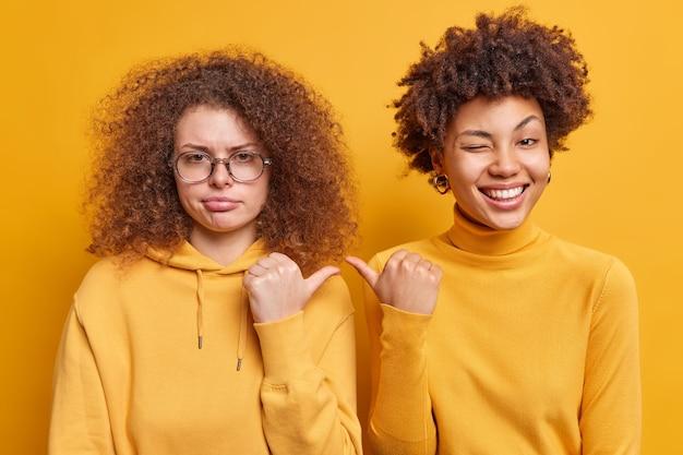 Vrolijke afro-amerikaanse vrouw en haar droevige zus met krullend haar wijzen duimen naar elkaar en drukken verschillende emoties uit, nonchalant gekleed geïsoleerd over gele muur. het is zij. twee vrouwen binnen