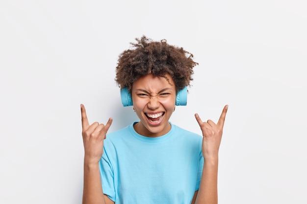 Vrolijke afro-amerikaanse vrouw geniet van rockmuziek maakt heavy metal gebaar glimlacht breed gebruikt stereo hoofdtelefoon gekleed in basic blauw t-shirt geïsoleerd over witte muur voelt wild en vrij