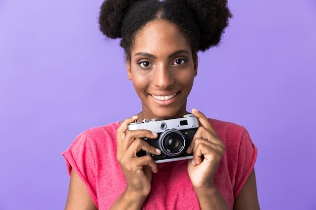 Vrolijke afro-amerikaanse vrouw glimlachend en met retro camera, geïsoleerd